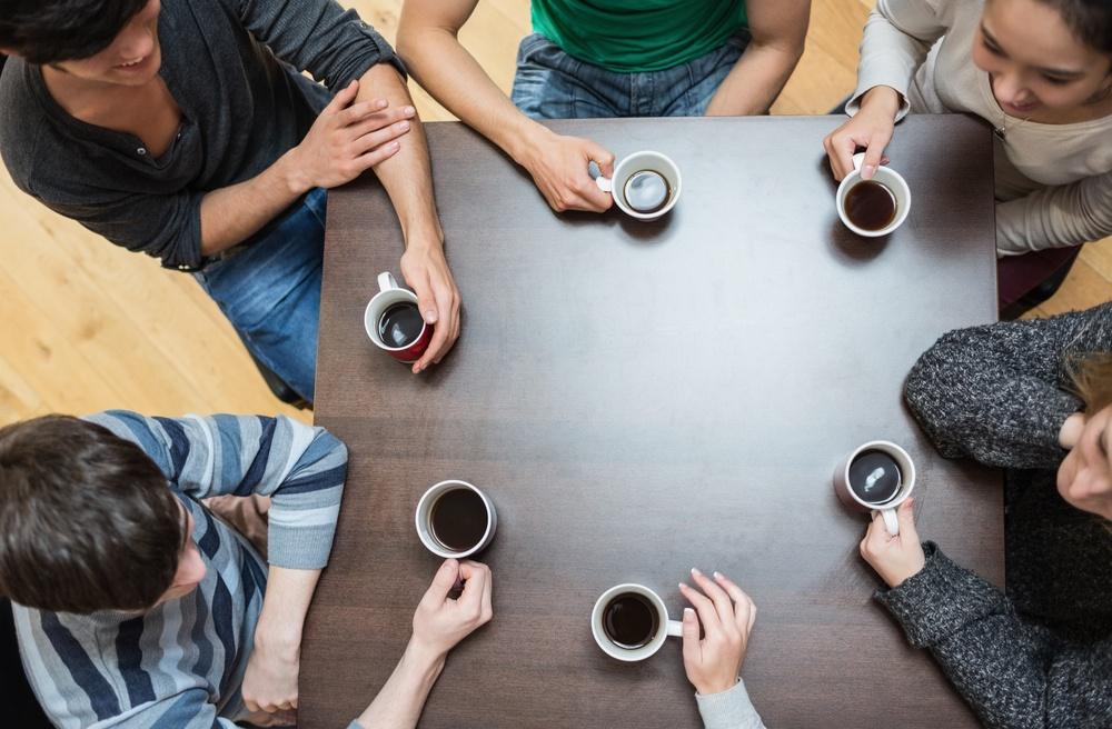 Ansatte tar seg en pust i bakken med hver sin kaffekopp