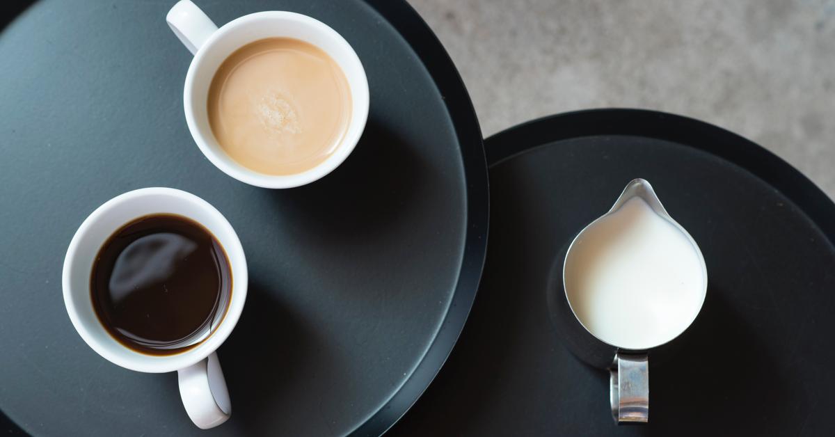To runde bord. end to kopper kaffe og en kanne melk. guide til kaffe på jobben.