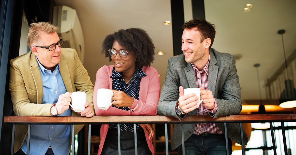 Kollegaer som henger over et rekkverk å drikker kaffe.