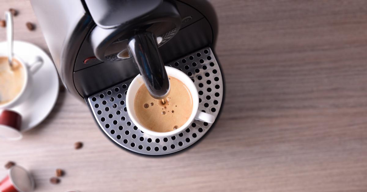 Liten kaffemaskin på jobb med en fersk kopp kaffe