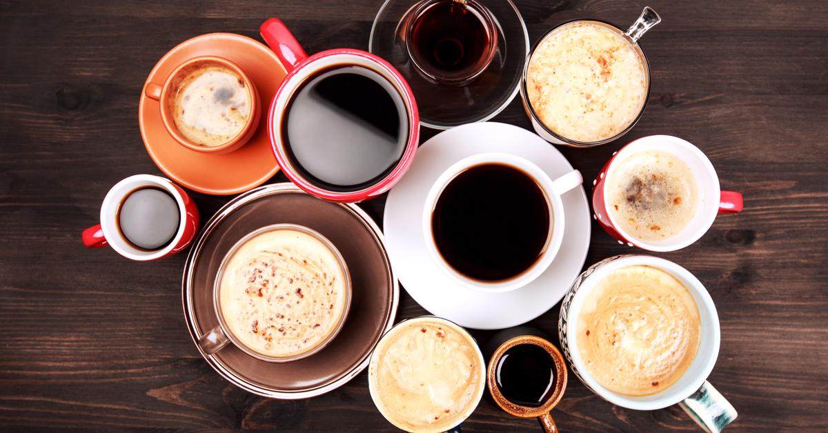 Mange fargerike kaffekopper samlet i en ring på et bord. Guide til kaffe på jobben.