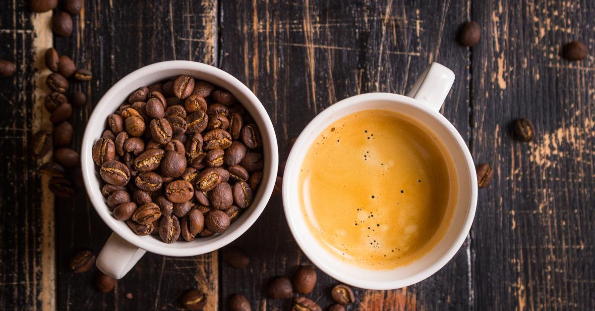 En kopp med kaffebønner og en kopp med kaffe på en brun treplate. Guide til kaffe på jobben.