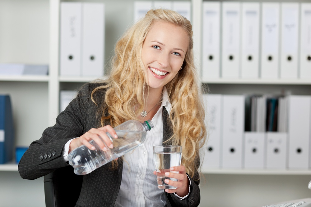 Portrait of happy businesswoman pouring water in glass from bottle at office