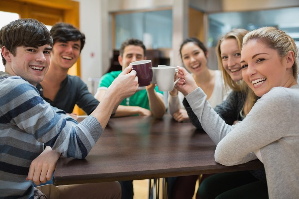 Students sitting clinking cups while smiling in college cafe.jpeg