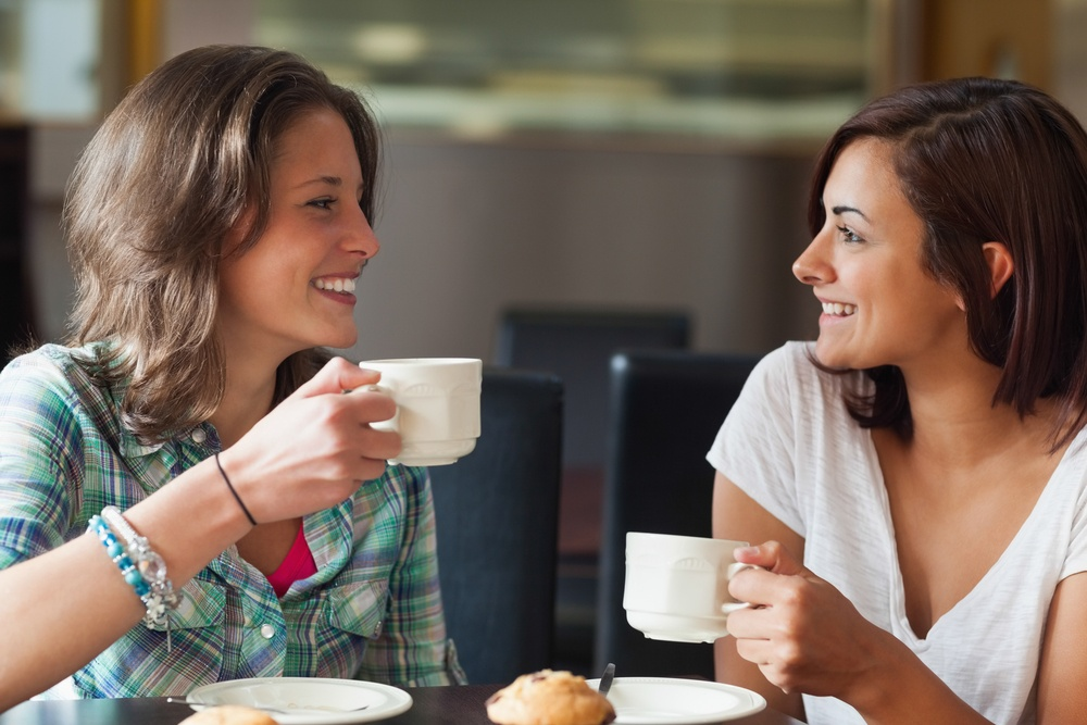 Two smiling students having a cup of coffee in college canteen.jpeg